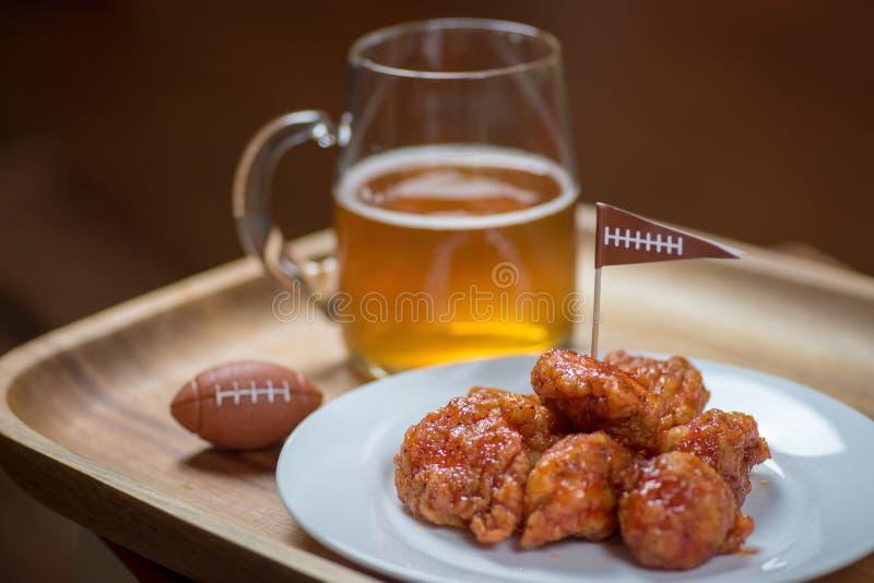 Alas calientes sin hueso en la placa con la taza de cristal de cerveza y de fútbol imágenes de archivo libres de regalías