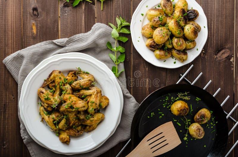 Alas de pollo asadas con la nueva patata imágenes de archivo libres de regalías