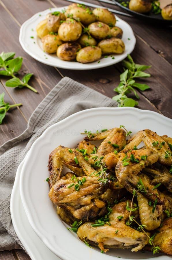 Alas de pollo asadas con la nueva patata fotos de archivo