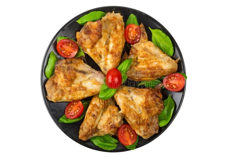 Alas de pollo asadas a la parrilla con los tomates y albahaca en un plato negro aislado en el fondo blanco fotos de archivo libres de regalías