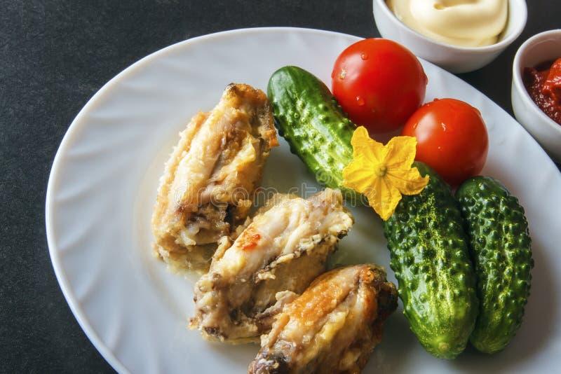 Alas de pollo cocidas en pasta de tomate y mayonesa en una placa blanca con las verduras orgánicas frescas en un fondo negro Copi fotografía de archivo