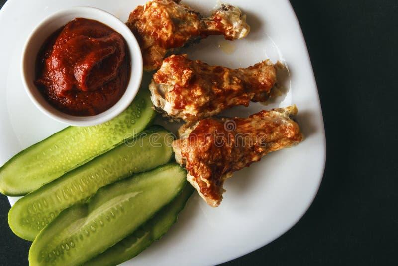 Alas de pollo cocidas de las aves de corral, pasta de tomate y pepinos cortados en una placa blanca en un fondo negro Visión supe imagen de archivo