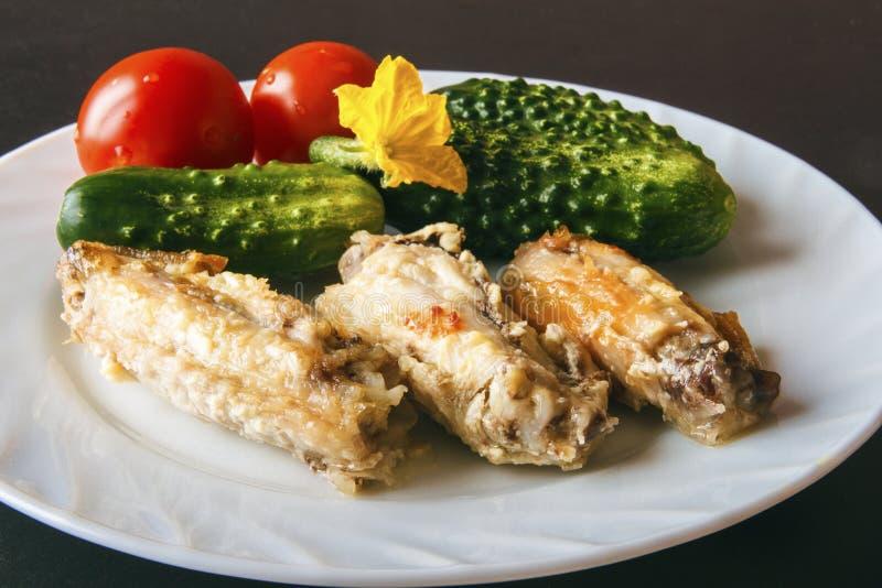 Alas de pollo cocidas de las aves de corral, tomates frescos y pepinos verdes en una placa blanca en un fondo negro Comida sana s imagenes de archivo