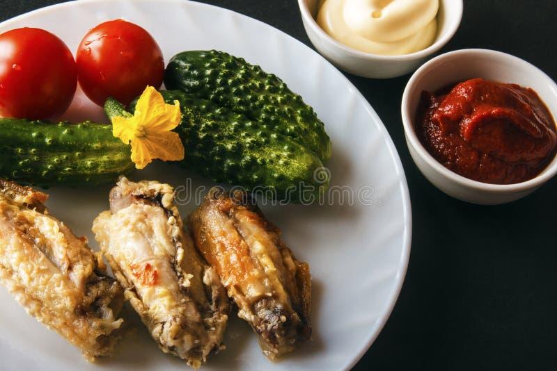 Alas de pollo cocidas, mayonesa, pasta de tomate y verduras orgánicas frescas en una placa blanca en un fondo negro Sano dietétic imagen de archivo