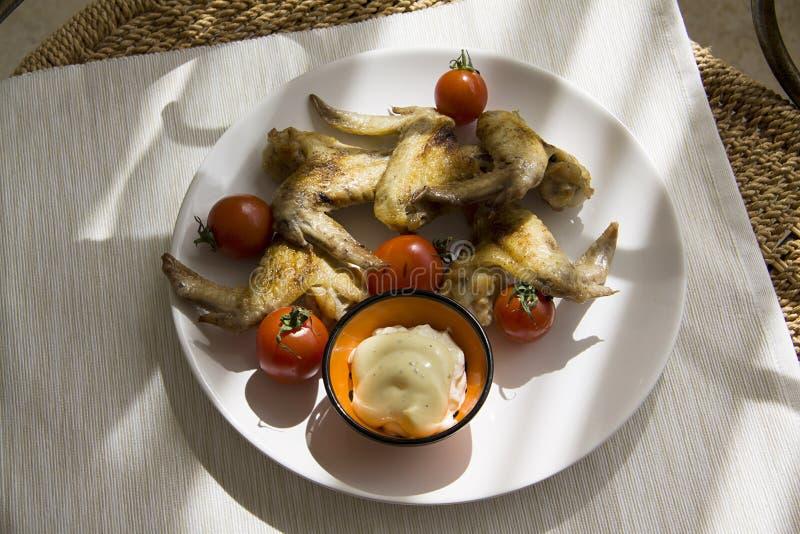 Alas de pollo con el tomate con el relámpago del día del contraste fotos de archivo libres de regalías