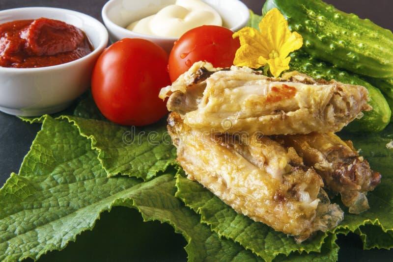 Alas de pollo deliciosas cocidas en pasta de tomate y mayonesa en las hojas verdes de un pepino con las verduras orgánicas fresca imagenes de archivo