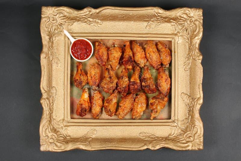 Alas de pollo en un marco, visión desde arriba foto de archivo