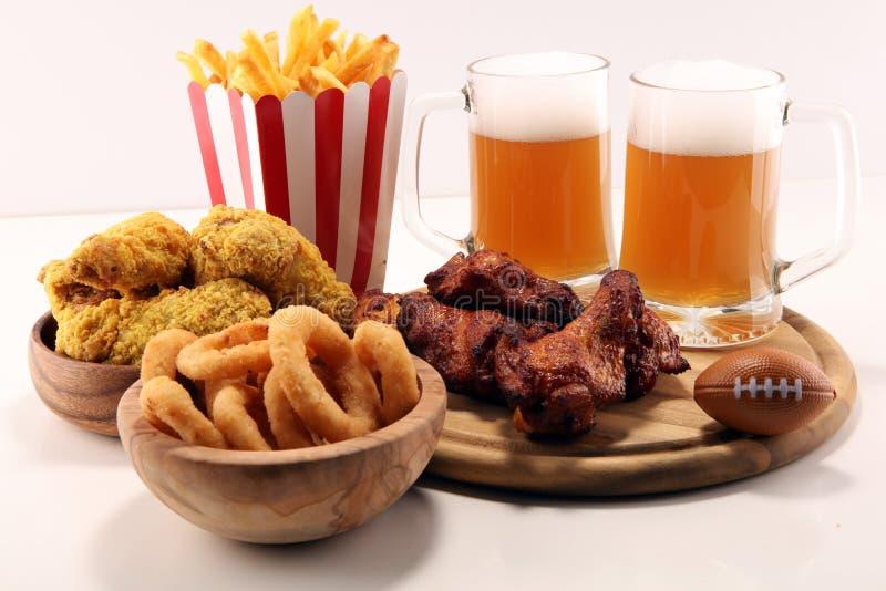 Alas de pollo, fritadas y anillos de cebolla para el fútbol en una tabla Grande para el juego del cuenco fotografía de archivo libre de regalías