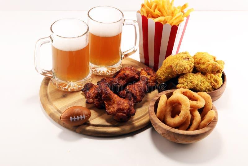 Alas de pollo, fritadas y anillos de cebolla para el fútbol en una tabla Grande para el juego del cuenco imagen de archivo libre de regalías