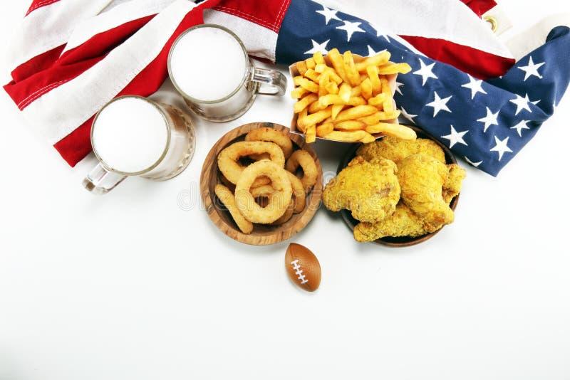 Alas de pollo, fritadas y anillos de cebolla para el fútbol en una tabla Grande para el juego del cuenco fotos de archivo libres de regalías