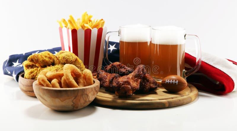 Alas de pollo, fritadas y anillos de cebolla para el fútbol en una tabla Grande para el juego del cuenco fotos de archivo