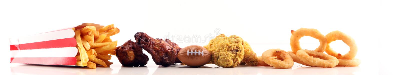 Alas de pollo, fritadas y anillos de cebolla para el fútbol en una tabla Grande para el juego del cuenco imagenes de archivo