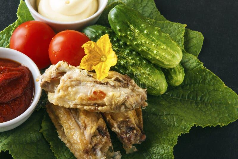 Alas de pollo frito con el pepino y los tomates frescos en las hojas verdes de un pepino en un fondo negro Copie el espacio fotos de archivo