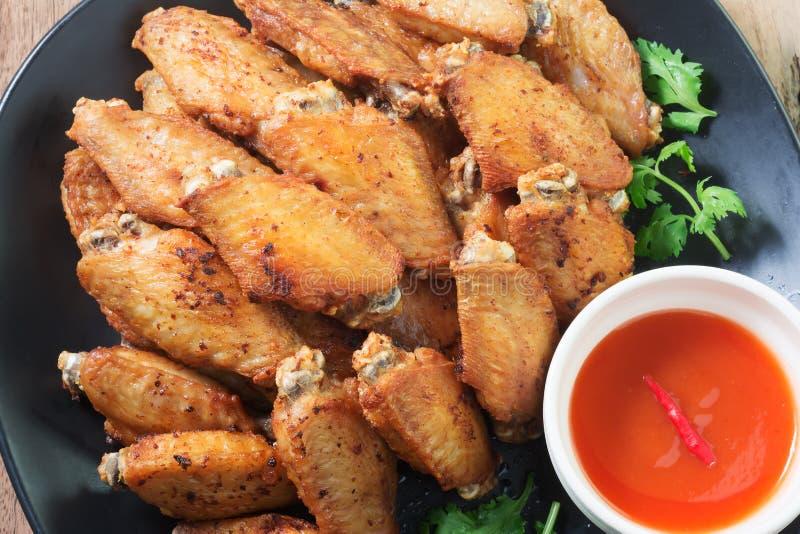 Alas de pollo frito en una placa con la salsa de pimienta negra fotos de archivo libres de regalías