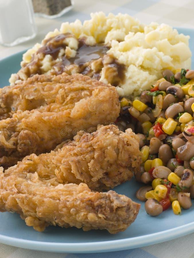 Alas de pollo frito meridionales con la patata de puré imagenes de archivo
