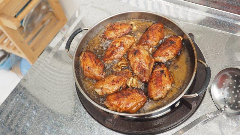 Alas de pollo que cocinan la cacerola frita y el equipo imágenes de archivo libres de regalías