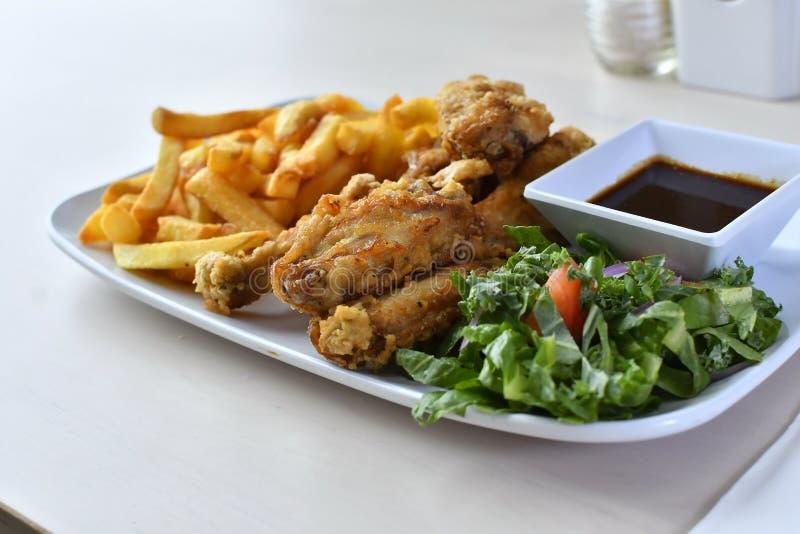 Alas de pollo y patatas fritas con la ensalada 3 fotos de archivo libres de regalías