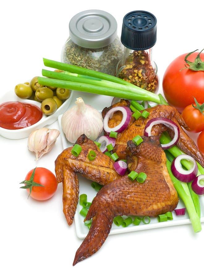 Alas, verduras y especias de pollo ahumadas en un backgroun blanco fotos de archivo