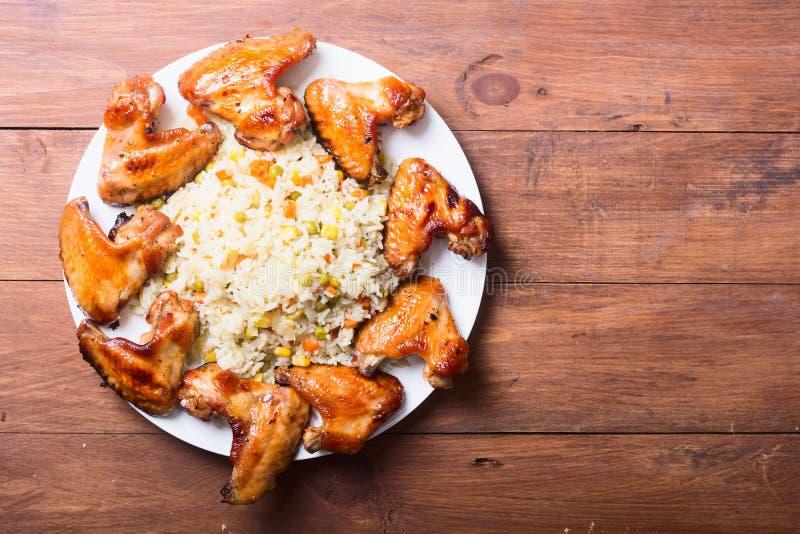 Alas y arroz asados a la parrilla de pollo imagen de archivo libre de regalías