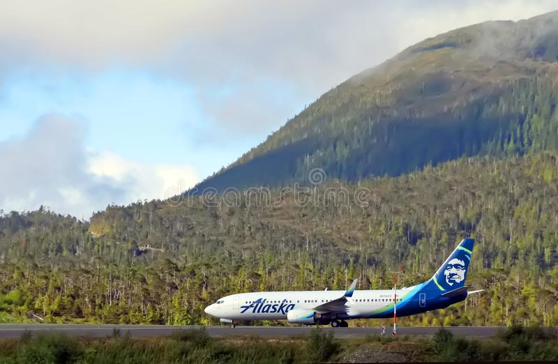 Alaska Airline with scenic View. Alaska Airline as seen from a cruise ship, on its way to Ketchikan, Alaska. In the background scenic view of mountain and trees stock photography