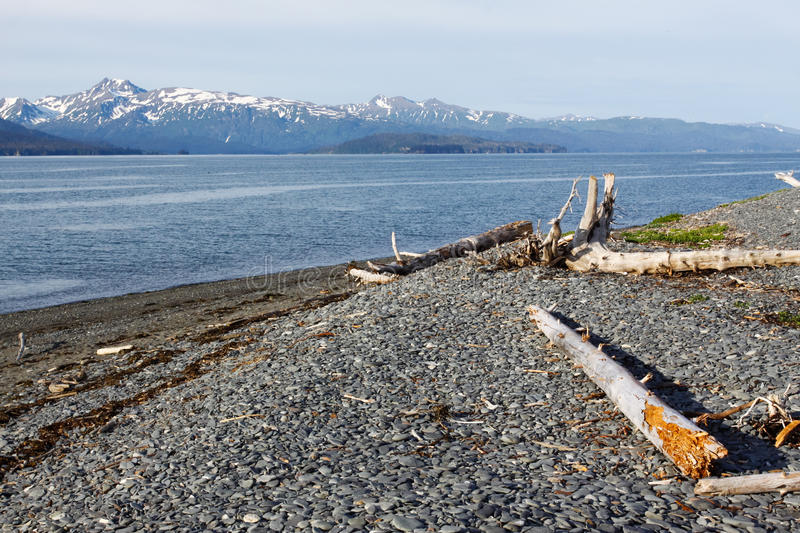 Alaska - End of the Homer Spit. A view from the rocky beach at the very end of the Homer Spit looking across Kachemak Bay towards the snow coverd Kenai mountains royalty free stock photography