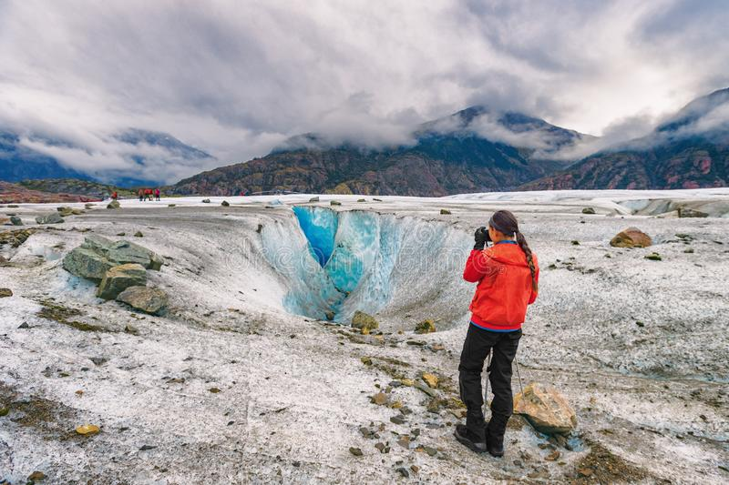 Alaska glacier hike walk tour woman tourist hiker taking pictures on cruise ship excursion. Helicopter ride. Girl walking on blue ice wilderness nature, popular stock photo