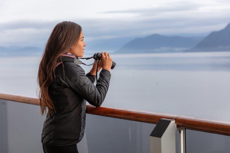 Alaska kryssningkvinna på hållande ögonen på fartygutfärd för val att turnera att se djurliv med kikare Turist på den inre passag arkivfoton