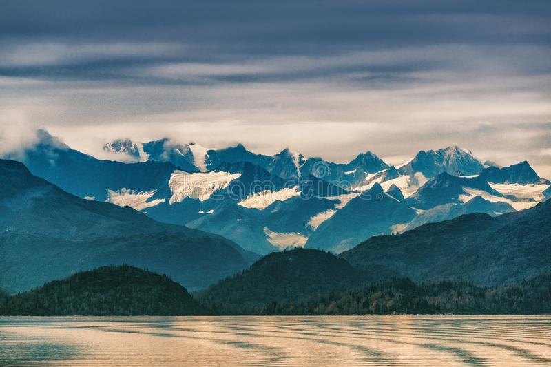 Alaska mountains range snow capped peaks in inside passage, Glacier bay nature landscape at autumn sunset dusk. View from cruise stock photos