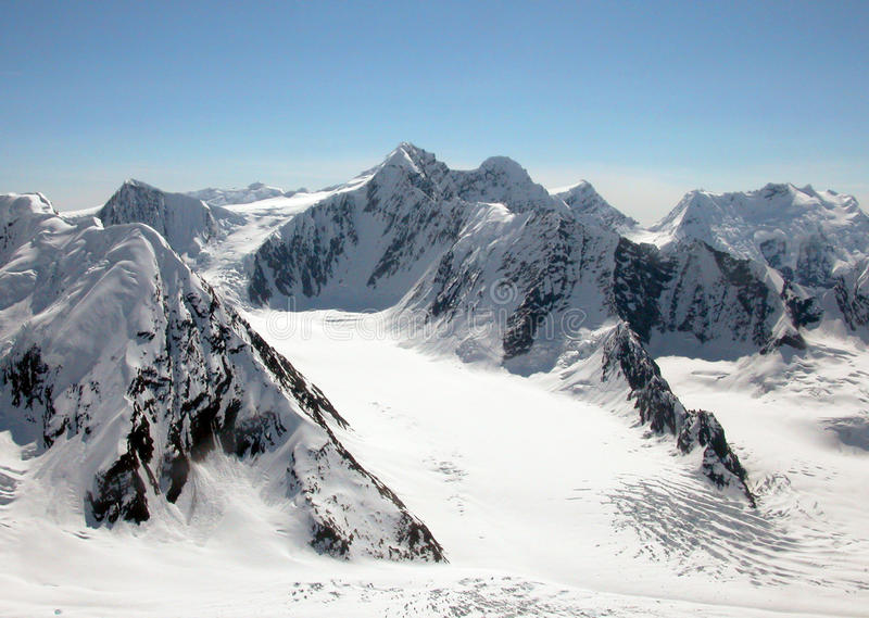 Alaska Mountains. Rocky peaks and glaciers of Alaska mountains. The picture of the plane royalty free stock photos