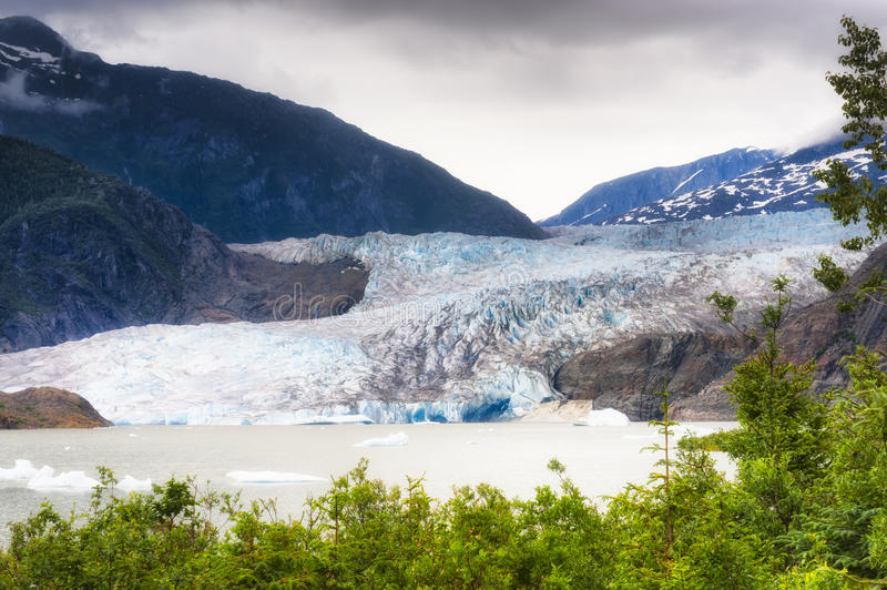 Alaska`s Mendenhall Glacier in Juneau. Mendenhall Glacier under cloudy skies in Tongass National Forest in Alaska. Proglacial lake with chunks of ice floating on royalty free stock photos