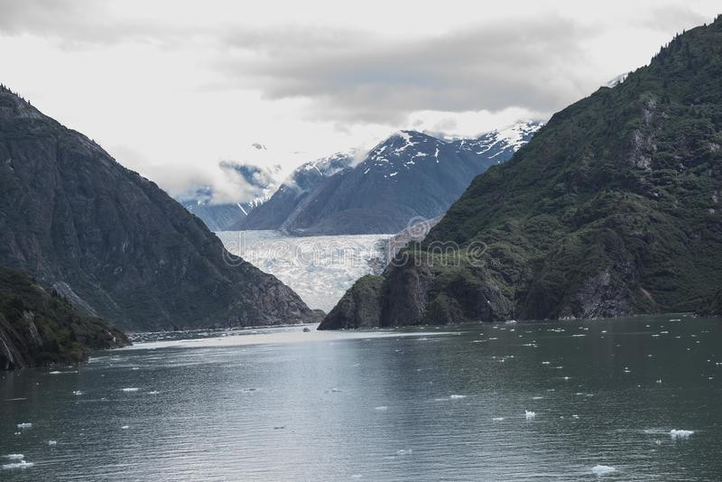Alaska snowcapped mountains with a glacier. With two large green covered hills and big puffy clouds with blue ocean in the foreground royalty free stock photography