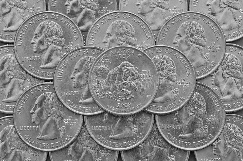 Alaska State and coins of USA. Pile of the US quarter coins with George Washington and on the top a quarter of Connecticut State royalty free stock photos