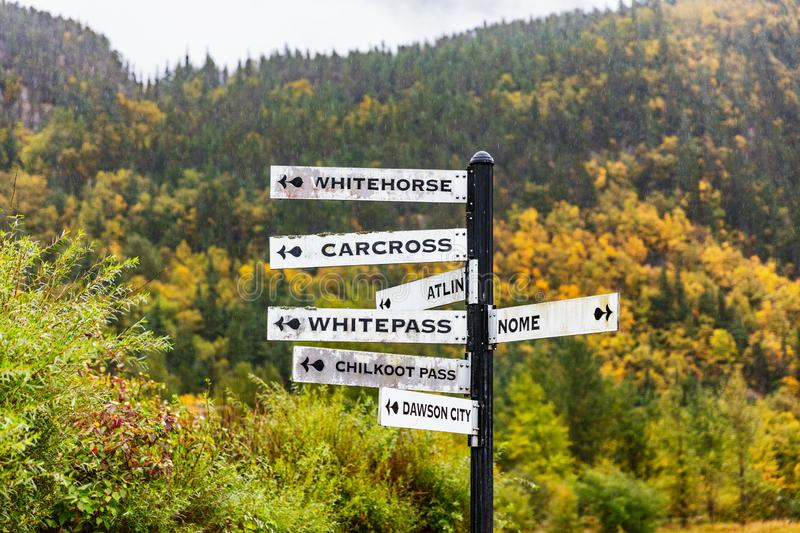 Alaska tourist street signs showing directions of different nearest tourism cities destination. Chilkoot, Whitehorse, Juneau,. Skagway. Road sign in Skagway stock photo