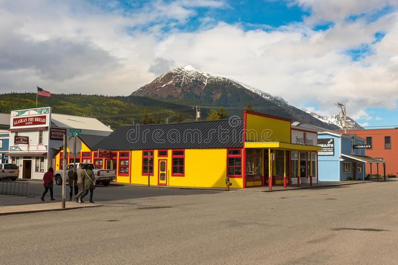 The Small Alaskan Town of Skagway. Alaska, USA -- April 29, 2016. Tourists walk down the street in Skagway, Alaska doing some sightseeing. Snow capped mountain stock images