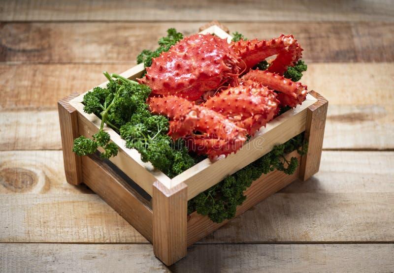 Alaskabo ånga för konung Crab Cooked eller kokt skaldjur på grön lockig persilja i träask med träbakgrund - ny röd krabba royaltyfria foton
