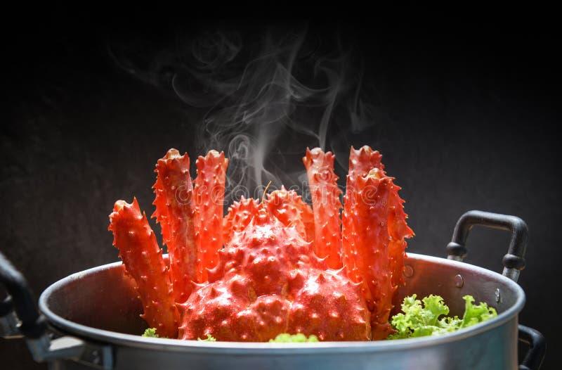 Alaskabo ångaremat för konung Crab Cooked på att ånga krukaskaldjur och grönsallatgrönsaken med mörk bakgrund - röd krabba hokkai royaltyfria bilder