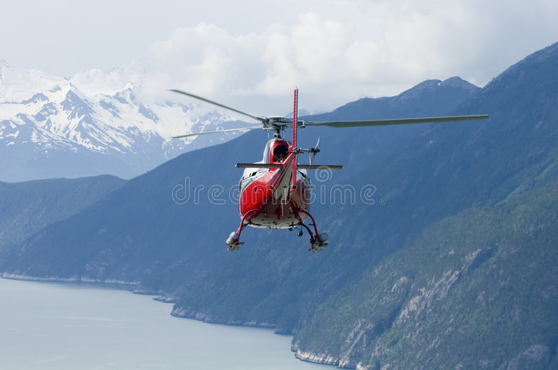 Alaskan Helicopter Series. A red and silver rescue helicopter flies across a remote glacier in Southeastern Alaska royalty free stock photography