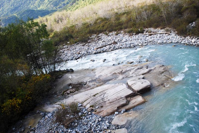 Alaskan Landscape with a Rockbed In The Creek. Alaskan landscape with a twisting creek through the mountains. The water is from glaciers, so it`s pale green and stock images