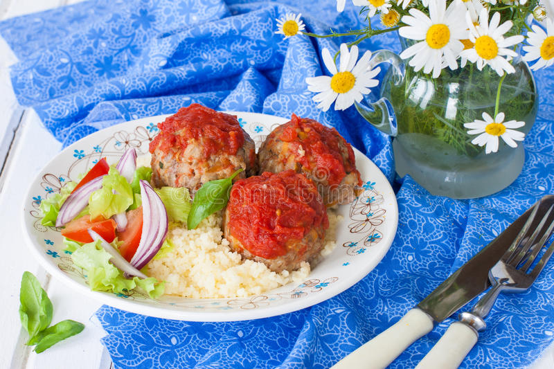 Albóndigas con la salsa de tomate, verduras y un acompañamiento del cuscús imágenes de archivo libres de regalías