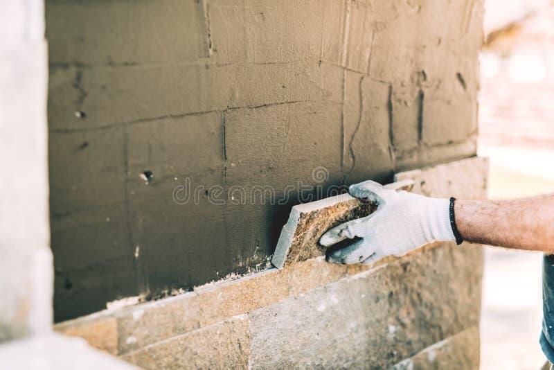 Albañil del trabajador que coloca de cerca la teja de piedra en la pared vertical Detalles de la industria - emplazamiento de la  imagen de archivo libre de regalías