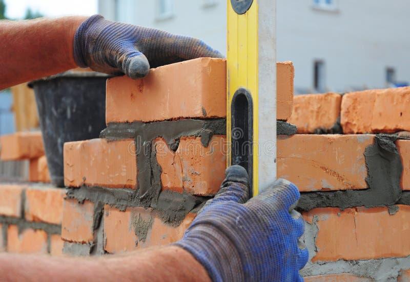 Albañil Using un nivel de alcohol para comprobar la nueva pared de ladrillo roja al aire libre Técnicas de la albañilería de los  imagen de archivo