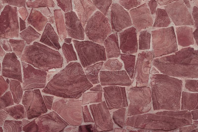 Albañilería marrón Textura de la pared de piedra roja Fondo de piedra abstracto Primer moderno de la pared de piedra rosada de la foto de archivo