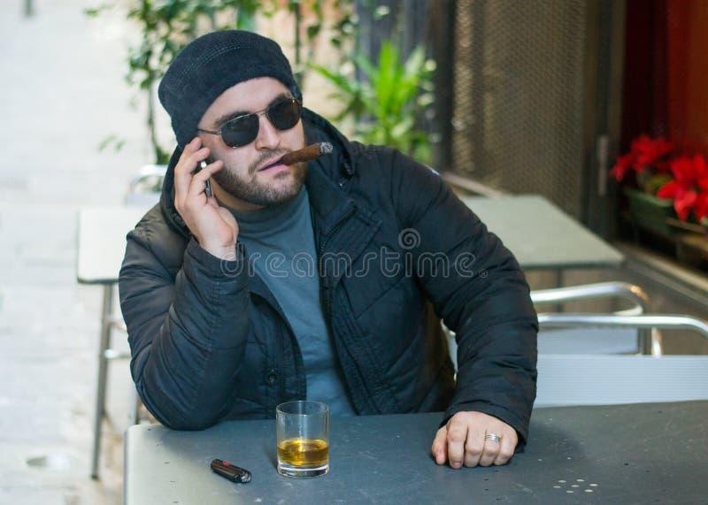 Albańska mafia kupuje cygaro i rozmawia przez telefon fotografia stock