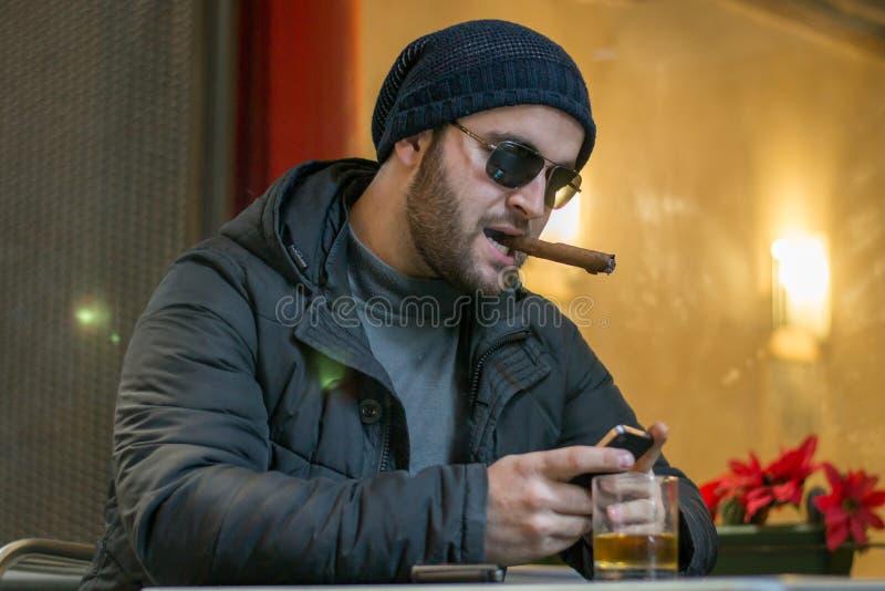 Albańska mafia kupuje cygaro i wygląda na smartfon. obrazy royalty free