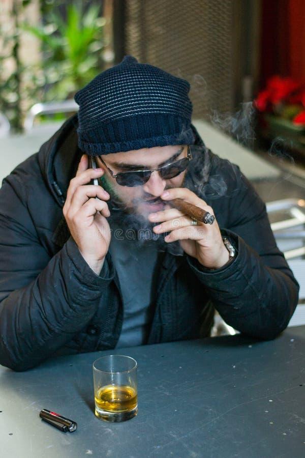 Albańska mafia kupuje cygaro i wygląda na smartfon. zdjęcia stock