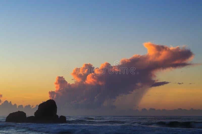 Alba ad una spiaggia rocciosa con le nuvole porpora immagini stock libere da diritti