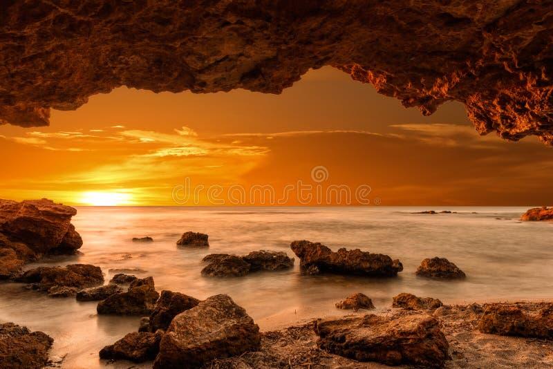 Alba al mare da una caverna fotografia stock