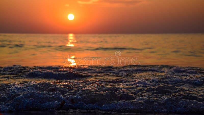 Alba alla riva del mare e dell'oceano, veduta dal livello della sabbia, con l'onda d'ardore di acqua e bokeh piacevole fotografie stock