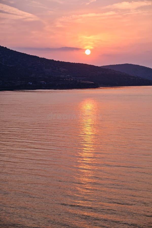 Alba arancio radiante, riflessioni in mare, Grecia fotografie stock