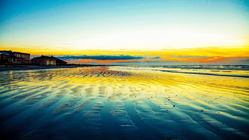 Alba che riflette luce dorata fuori da una spiaggia libera fotografia stock